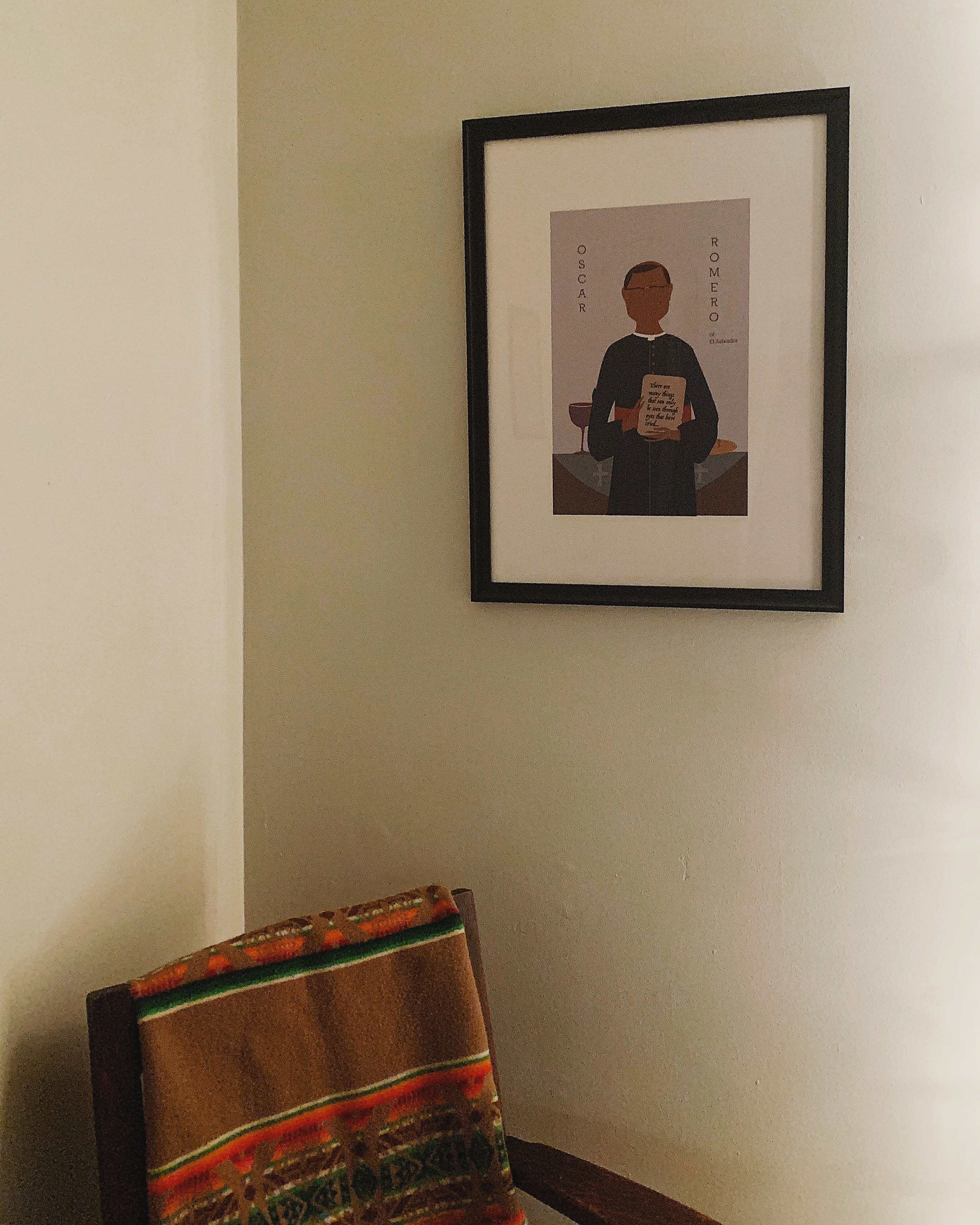 Framed print by Sarah Duet of Oscar Romero above a brown chair with a Pendleton blanket draped over the chair.